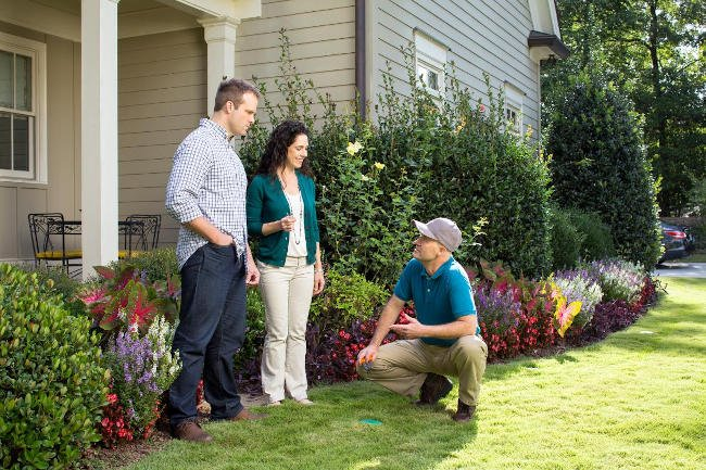 Couple talking to outdoor pest control worker